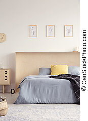 Yellow pillow and blanket on blue bed in bright bedroom interior with posters. Real photo