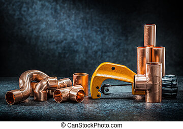 yellow pipe cutter and copper pipe with connectors on dark background