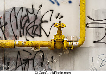 Yellow pipe with a faucet valve on the street wall