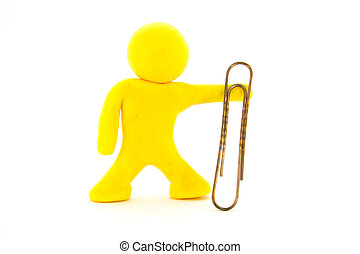Yellow plasticine character and big paperclip. Stationery. Isolated over white background