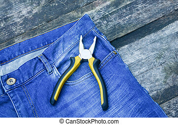 Yellow pliers in a pocket of blue jeans. Nippers Tools for general repair. Building