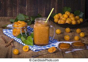 Yellow plum smoothie in glass, jam and ripe yellow plum on wooden table. Bio healthy food and drink