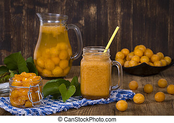 Yellow plum smoothie in glass, lemonade, jam and ripe yellow plum on wooden table. Bio healthy food and drink