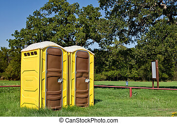 Yellow portable toilets - Two yellow portable toilets at a...