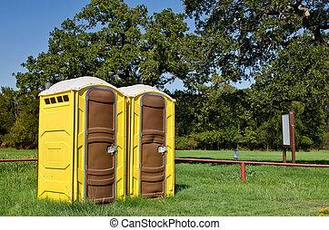 Yellow portable toilets - Two yellow portable toilets at a...