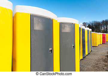 portable toilets - yellow portable toilets under a nice ...