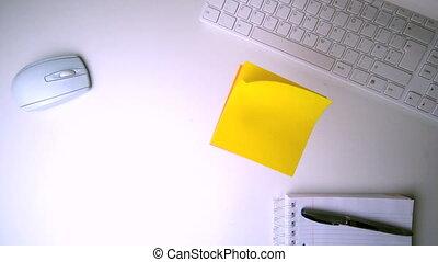 Yellow post it falling on office de