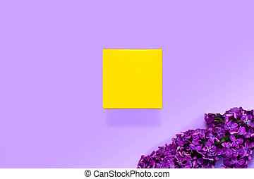 Yellow present box with branch of lilac on a purple background