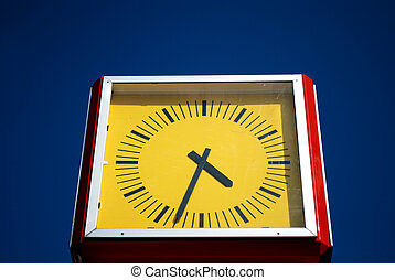 yellow public clock in front of blue sky
