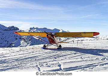 Yellow red airplane at the mountain airfield in swiss alps...