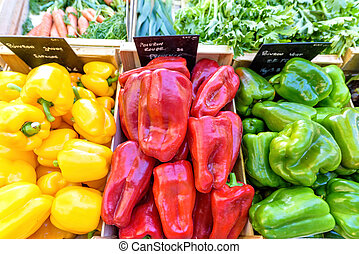 Yellow, red and green peppers for sale in local marketplace