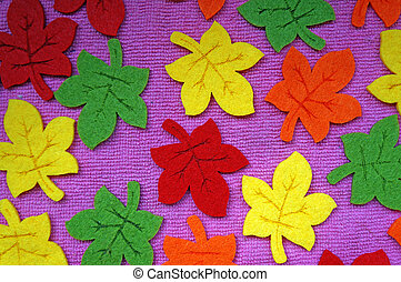 Yellow, red, orange and green Maple leaves out of felt on fabric