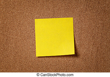 yellow reminder sticky note on cork board, empty space for...