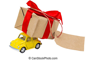 Yellow retro toy car delivering gifts box with tag with empty space for a text on white background