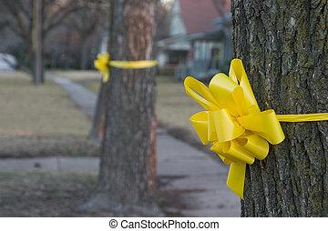 Yellow Ribbon Around An Old Oak Tree 1 - Closeup of a yellow...