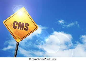 Yellow road sign with a blue sky and white clouds: cms