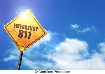 Yellow road sign with a blue sky and white clouds: emergency 911
