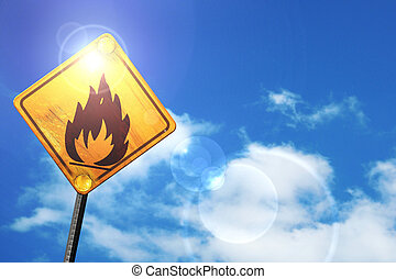 Yellow road sign with a blue sky and white clouds: Flammable haz