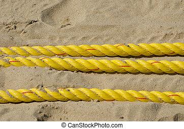 yellow ropes on resort beach sand