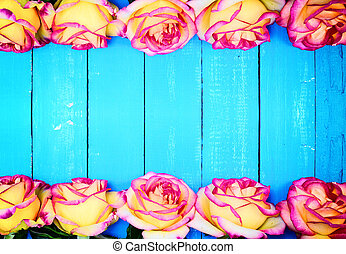 yellow roses on a blue wooden background