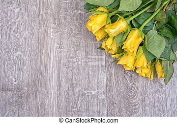 Yellow roses on a wooden background