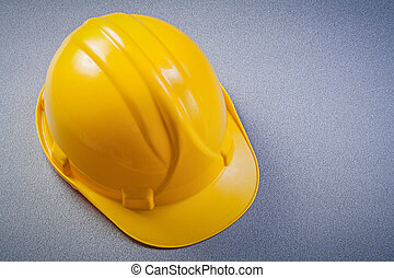 Yellow safety construction helmet on grey background maintenance