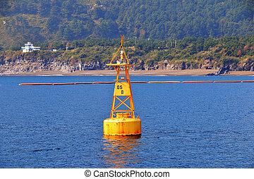 yellow sea buoy in blue sea