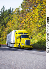 Yellow semi truck and reefer trailer driving uphill autumn road