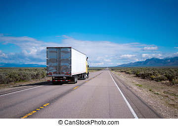 Yellow semi truck drive with commercial cargo by Nevada road