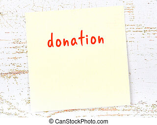 Yellow sheet of paper with word donation. Reminder concept