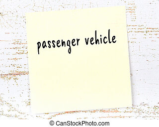Yellow sticky note on wooden wall with handwritten inscription passenger vehicle