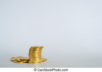 Yellow shiny coins are stacked on a light gray blue background