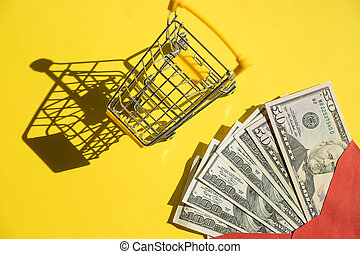 yellow shopping cart and dollar bills on yellow background close-up. Concept of finance, online shopping, high cost of medicines. Concept for online marketing or shopping budgeting.Copy space