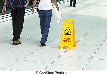 Yellow sign that alerts for wet floor. - Yellow sign that...