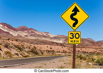 Yellow sign with curved arrow and road, California
