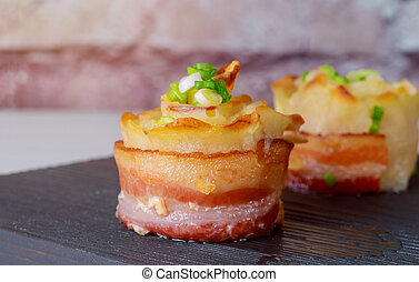 Yellow sliced potatoes with bacon cooked in the oven