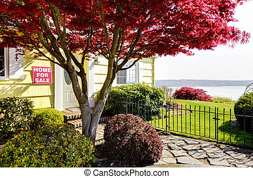 Yellow small home with water view and red maple. For sale.