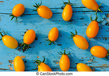 Yellow small tomatoes on blue wooden surface. top view.
