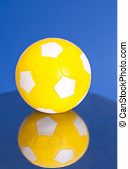 Yellow Soccer Ball with reflection on blue background