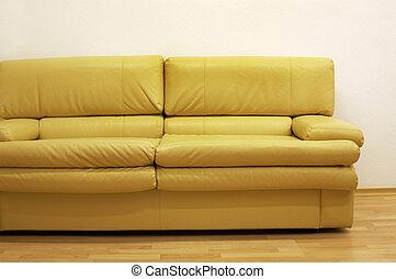 Yellow sofa at a wall at modern office