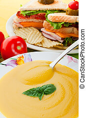 Yellow soup and sandwich