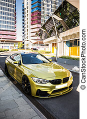 Yellow sport car parked at the side of the central road, upside view