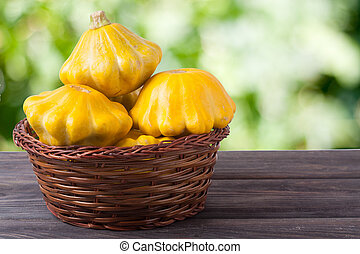 yellow squash in a wicker basket on  wooden table