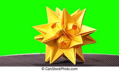 Yellow star origami figurine on green background.