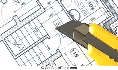 Yellow stationery knife on building plan, rotation, close up