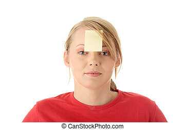 Young woman in red tshirt with yellow sticky note on forehead. Isolated.