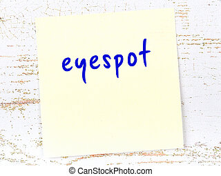 Yellow sticky note on wooden wall with handwritten inscription eyespot