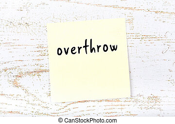 Concept of reminder about overthrow. Yellow sticky sheet of paper on wooden wall with inscription