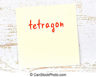 Yellow sticky note on wooden wall with handwritten inscription tetragon