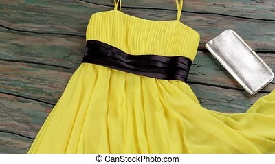 Yellow summer dress and purse. Dress with silver clutch bag. Bright garment on green table. Quality goods sold at retail.